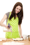 Baking woman pouring flour on a table. Happy baking woman pouring flour on a table with white background Royalty Free Stock Photography