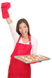 Baking woman on white background. Baking woman excited with arm raised in success holding a tray of cookies. Young smiling Asian / Caucasian woman isolated on Royalty Free Stock Photos