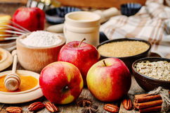 Baking wood background with apples, nuts, honey, flour and butte Royalty Free Stock Images
