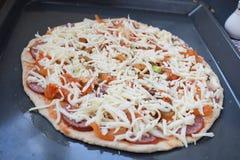 Bakkende ruwe pizza, smakelijke eigengemaakte kaaspizza stock foto