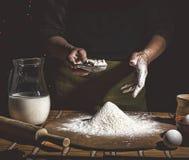 bakkerij Mens die brood, Pasen-cake, Pasen-brood of dwars-broodjes op houten lijst in een bakkerij dicht omhoog voorbereiden Mens royalty-vrije stock fotografie
