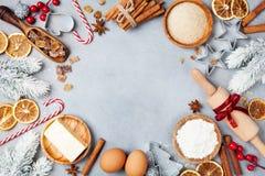 Bakkerijachtergrond met ingrediënten voor het koken Kerstmisbaksel met spar worden verfraaid die Bloem, bruine suiker, eieren en  stock foto