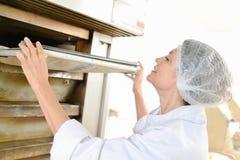 Bakkerijarbeider die door oven wordt bevonden royalty-vrije stock fotografie