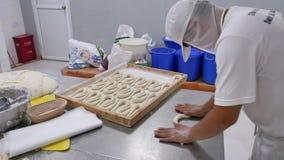 Bakkerijarbeider die en deeg voor pretzels rollen vormen stock video