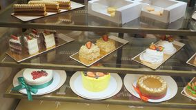 Bakkerijvitrine met cakes en gebakjes op glasplanken stock video
