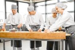 Bakkers die deeg voor baksel vormen bij de productie royalty-vrije stock foto