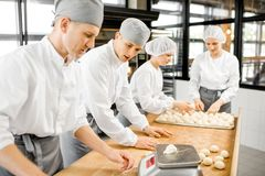 Bakkers die deeg voor baksel vormen bij de productie stock afbeeldingen
