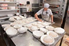 Bakkers die met de hand gemaakte broden van brood in een familiebakkerij maken die het deeg vormen in tradionalvormen in Sofia, B stock foto