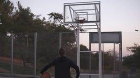Baklängd i fot räknat av en kvinnlig spelare för ung basket som joggar med bollen på det fria, uppvaktar och kastar den till besl lager videofilmer