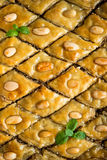 Baklava with almonds and honey. Background. Background with honey baklava, decorated with mint Stock Photo