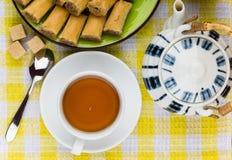 Baklava auf Platte, Zucker und Tee auf gelber Tischdecke Lizenzfreie Stockbilder
