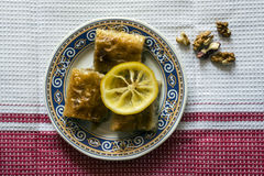 Baklava / Baqlawa / Baklawa dessert. Baklava dessert decorated with lemon slice and walnuts. Top view Stock Images