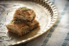 Baklava com pistache em uma bandeja dourada com testes padrões orientais Fotos de Stock