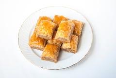 Baklava dulce en la placa en el fondo blanco fotografía de archivo