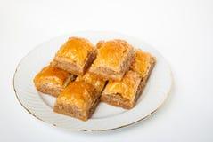 Baklava dulce en la placa en el fondo blanco fotos de archivo