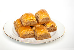 Baklava dulce en la placa en el fondo blanco imagen de archivo libre de regalías