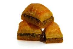 Baklava med pistascher, valnötter och honung på vit bakgrund Fotografering för Bildbyråer