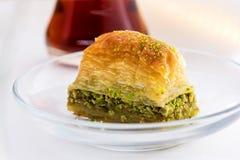 Baklava met pistache en Turkse kop thee op een witte achtergrond Royalty-vrije Stock Foto's