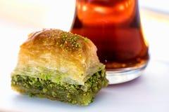 Baklava met pistache en Turkse kop thee op een witte achtergrond Stock Foto's