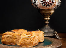 Baklava. Pieces served on a rustic plate.  is a popular sweet in the Middle East made from many layers of filo pastry and filled with nuts soaked in syrup Stock Images