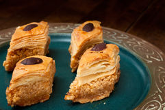 Baklava. Pieces served on a rustic plate.  is a popular sweet in the Middle East made from many layers of filo pastry and filled with nuts soaked in syrup Royalty Free Stock Images