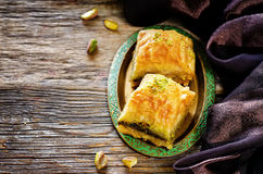 Baklava with pistachio. turkish traditional delight. On a dark wood background. toning stock photo