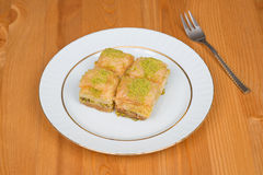 Baklava with pistachio. turkish traditional delight on a wood background. Stock Image