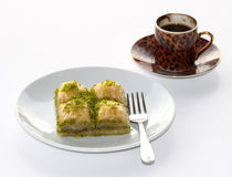 Baklava with pistachios and a cup of Turkish Coffee on white. Turkish Style Baklava with pistachios served with cup of Turkish Coffee on white royalty free stock images