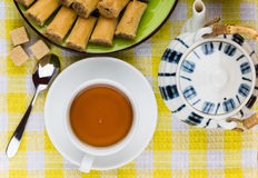 Baklava on plate, sugar and tea on yellow tablecloth Royalty Free Stock Images