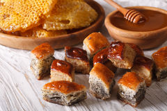Baklava with poppy and nuts close-up and a honeycomb. Horizontal Royalty Free Stock Images
