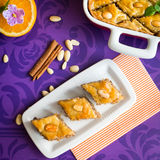 Baklava with walnut and almonds. Pieces of sweet honey baklava with walnut and almonds on purple background. Square image Stock Image
