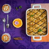Baklava with walnut and almonds. Sweet honey baklava with walnut and almonds on purple background. Square image with many details Stock Image