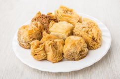 Baklava in white plate on wooden table Stock Photos