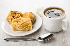 Baklava in white saucer, coffee in cup, sugar and spoon Stock Photo