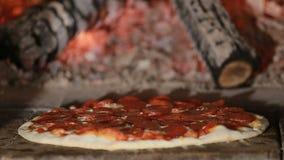 Bakning för peperonipizza i trä avfyrad ugn lager videofilmer