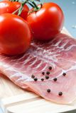 Bakon and tomatoes. Cutted bakon, tomatoes and black pepper on the wooden board Stock Photography