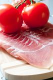Bakon and tomatoes. Cutted bakon and tomatoes on the wooden board Stock Image
