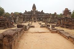 Bakong temple ruins. Tourists are visiting the Bakong temple ruins, Angkor, Siem Reap, Cambodia. The temple is part of the Roluos group, that include three Royalty Free Stock Photo