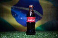 BAKOU, AZERBAÏDJAN - 1ER JUILLET 2018 : Concept créatif Classique de Coca-Cola dans une bouteille en verre sur l'herbe Soutenez v Photographie stock libre de droits