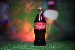 BAKOU, AZERBAÏDJAN - 1ER JUILLET 2018 : Concept créatif Classique de Coca-Cola dans une bouteille en verre sur l'herbe Soutenez v Images libres de droits