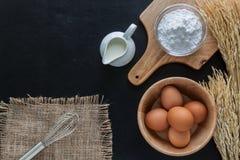 Bakpulver mjölkar och ägg på den svart tavlan för bakgrund Arkivfoto