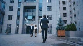 Bakre bild av en framgångsrik kaukasisk affärsman i kostym som går på gatan på kontorscentralen och talar på telefon lager videofilmer