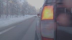 Bakre lampa SUV på vintervägen, rött ljus Stäng sig upp av den stora svarta bilen från bakre sikt på en vinterväg arkivfilmer