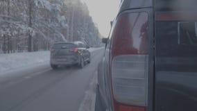 Bakre lampa SUV på vintervägen, rött ljus Stäng sig upp av den stora svarta bilen från bakre sikt på en vinterväg lager videofilmer