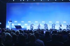 Bakre sikt av åhörare över högtalarna på etappen i mötet för konferenskorridor eller seminarium, affär och utbildning Arkivfoton