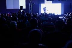 Bakre sikt av åhörare i mötet för konferenskorridor eller seminariumsom har högtalare på etappen, affären och utbildningen Fotografering för Bildbyråer