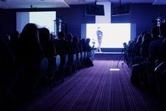 Bakre sikt av åhörare i mötet för konferenskorridor eller seminariumsom har högtalare på etappen, affären och utbildningen Royaltyfri Foto