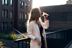 Bakre sikt av affärskvinnablicken på soluppgång ovanför stad Arkivbilder