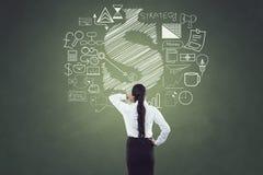 Bakre sikt av affärskvinnan med affärs- och finanssymboler Arkivfoton
