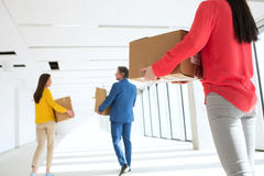 Bakre sikt av affärskvinnan med kollegor som bär kartonger som flyttar sig in i tomt kontor Arkivfoto